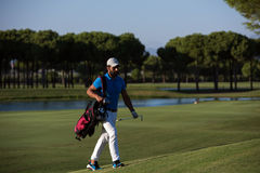 Golfer  walking and carrying bag Royalty Free Stock Photo