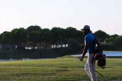 Golfer  walking and carrying golf  bag at beautiful sunset Royalty Free Stock Photography