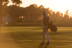 Golfer  walking and carrying golf  bag at beautiful sunset Stock Photos
