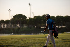 Golfer  walking and carrying golf  bag at beautiful sunset Royalty Free Stock Photos