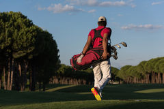 Golfer  walking and carrying golf  bag Stock Photos