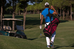 Golfer  walking and carrying golf  bag Royalty Free Stock Photography