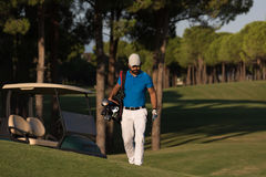 Golfer  walking and carrying golf  bag Royalty Free Stock Image