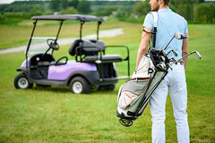 Golfer walking with golf bags. Ready for that hole in one. Close up of male golfer walking away while holding golf back, standing on green golf course with golf Stock Photography