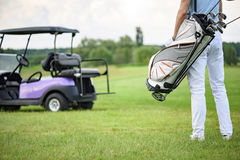 Golfer walking with golf bags Stock Photos