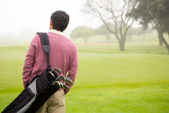 Golfer walking and holding his golf bags Stock Images