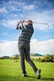 Golfer women. Pretty young lady golfer view from below against a blue sky Royalty Free Stock Image