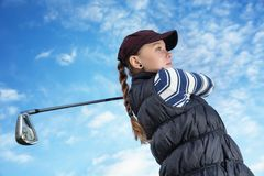 Golfer women. Pretty young lady golfer view from below against a blue sky Royalty Free Stock Photography