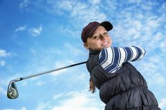 Golfer women. Pretty young lady golfer view from below against a blue sky Stock Images