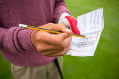 Golfer writing his points in paper Stock Image