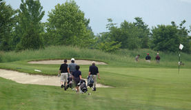 Golfers. Approaching the green stock images