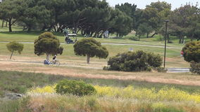 Golfers and bicyclists in the park stock video footage