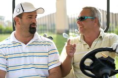 Golfers in cart. Two men in a golf cart argueing about the game royalty free stock photo
