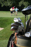 Golfers and Golfbag. Group of golfers putting on green with set of clubs in golf bag blurred in foreground. Vertical framing Stock Photos