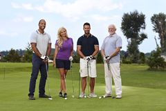 Golfers on the green. Diverse group of golfers standing on the green, smiling, looking at camera stock image