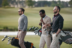 Golfers holding bags with golf clubs and walking on golf course. Multiethnic golfers holding bags with golf clubs and walking on golf course Stock Photography
