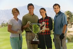Golfers Holding Their Winning Trophy. Group portrait of golfers holding their winning trophy on golf course Royalty Free Stock Images