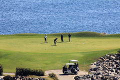 Golfers on ocean green in Mexico Stock Photography