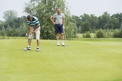 Golfers play the ball on the green Royalty Free Stock Images