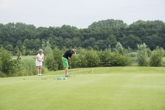 Golfers play the ball on the green Stock Photography