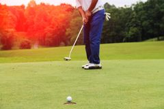 Golfers are putting golf in the evening golf course in Thailand. Golfers are playing golf in the evening golf course in thailand Royalty Free Stock Photo