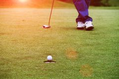 Golfers are putting golf in the evening golf course in Thailand. Golfers are playing golf in the evening golf course in thailand Stock Photo