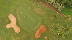 Golfers on Putting Green Tropical Golf Course Palm Trees. Two golfers finish up the ninth hole avoiding sand traps viewed from above stock footage