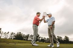 Golfers shaking hands at golf course after the game. Two senior friends shaking hands at golf course after the game. Professional golfers enjoying the game on stock images