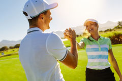 Golfers shaking hands at golf course. Happy male and female friends shaking hands at golf course after the game. Pro golfer enjoying the game on field Stock Image