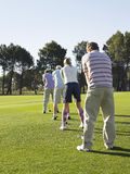 Golfers Standing In Row Teeing Off Royalty Free Stock Images