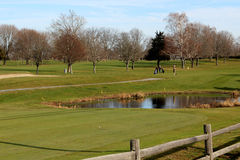 Golf course water hazard with golfers Stock Photography