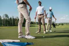 Golfers talking while standing and holding clubs on green pitch. Professional golfers talking while standing and holding clubs on green pitch Royalty Free Stock Photos