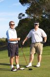 Golfers on the tee box. Young male golfer with his senior father ready to tee off on a beautiful summer day Stock Photos