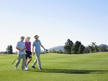 Golfers Walking On Golf Course. Three young golfers walking on golf course Royalty Free Stock Photography