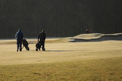 Golfers walking golf course in winter. Golfers on a picturesque golf course walking with their golf bags. Taken on 21-02-2018 Royalty Free Stock Image
