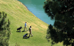 Golfers walking to their balls in a lake. Two golfers as seen from above, walking towards their golf balls in the lake royalty free stock image