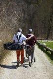 Golfeur d'homme et de femme marchant sur un terrain de golf Photos libres de droits