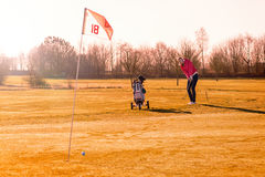 Golfeur de femme jouant un rond à la lumière du soleil de soirée Image stock