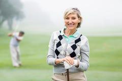 Golfeur de Madame souriant à l'appareil-photo avec l'associé derrière Photographie stock