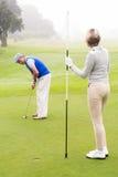 Golfeur de Madame tenant le drapeau pour l'associé mettant la boule Images libres de droits