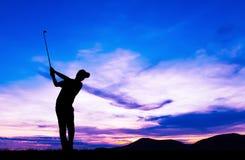 Golfeur de silhouette jouant le golf au beau coucher du soleil Image libre de droits