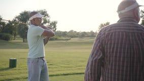Golfeur du Moyen-Orient beau balançant et frappant la boule de golf sur le beau cours Un homme plus âgé observe son adversaire et clips vidéos