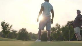 Golfeur du Moyen-Orient beau balançant et frappant la boule de golf sur le beau cours Un homme plus âgé observe son adversaire et banque de vidéos