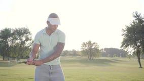 Golfeur du Moyen-Orient réussi de portrait balançant et frappant la boule de golf sur le beau cours Homme sûr jouant au golf deda clips vidéos