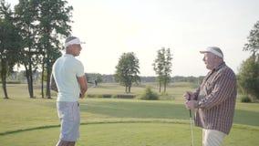 Golfeur du Moyen-Orient sûr balançant et frappant la boule de golf sur le beau cours Un homme plus âgé observe son adversaire banque de vidéos