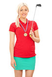 Golfeur féminin avec une médaille tenant un club de golf Image stock