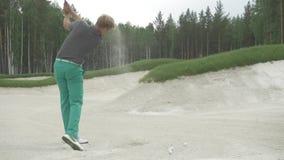 Golfeur frappant la boule avec le club sur le beau terrain de golf Le golfeur frappe un fairway tiré vers la maison de club Frapp banque de vidéos