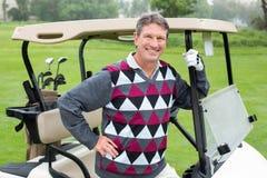 Golfeur heureux près du sien boguet de golf Image stock