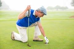 Golfeur heureux se mettant à genoux sur le putting green Photo libre de droits