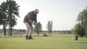 Golfeur mûr réussi de portrait balançant et frappant la boule de golf sur le beau cours Homme sûr jouant au golf dans beau banque de vidéos